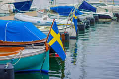 Boats lined up in a dock. Boats with the flag of Sweden lined up in a dock Stock Photo