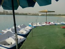 Boats Linewise In a Que With Umbrellas royalty free stock image