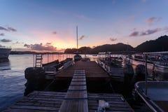 Boats at long docks at sunset stock photo