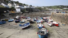Boats at low tide in summer Coverack harbour Cornwall England UK stock footage