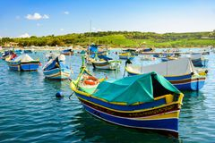 Boats Luzzu at Marsaxlokk harbor. Old Colorful Boats Luzzu in Marsaxlokk harbor at sunny day. Blue sky with clouds royalty free stock photography