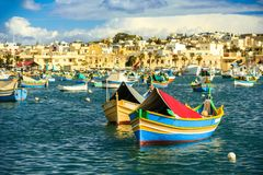 Boats Luzzu at Marsaxlokk harbor. Old Colorful Boats Luzzu in Marsaxlokk harbor at sunny day. Blue sky with clouds stock photography