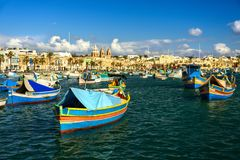 Boats Luzzu at Marsaxlokk harbor. Old Colorful Boats Luzzu in Marsaxlokk harbor at sunny day. Blue sky with clouds royalty free stock image
