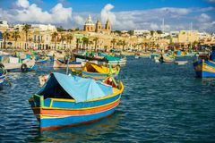 Boats Luzzu at Marsaxlokk harbor. Old Colorful Boats Luzzu in Marsaxlokk harbor at sunny day. Blue sky with clouds stock image