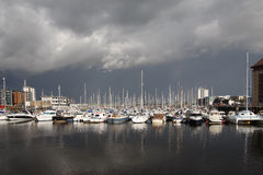 Boats in a marina with stormy sky. Boats in a marina with dark clouds, stormy sky stock photos