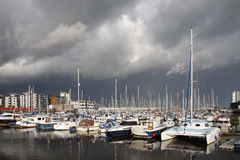 Boats in a marina, stormy sky. Boats in a marina with dark clouds, stormy sky stock photo