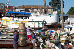 Boats market harbor river. Morning scene. Colorful boats in the market on the river, in Abaetetuba, Pará, Brazil. In the foreground, a man holds a pile of Royalty Free Stock Images
