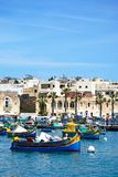 Boats in Marsaxlokk harbour, Malta. Traditional Maltese Dghajsa fishing boats in the harbour with waterfront buildings to the rear, Marsaxlokk, Malta, Europe Royalty Free Stock Photos