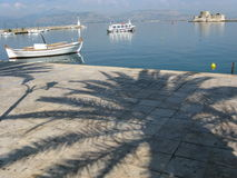 Boats in mediterranean port and palm shadow, NAFPLIO, GREECE. Boats in mediterranean port and palm shadow on pavement in the morning in warm and sunny summer day Stock Photography