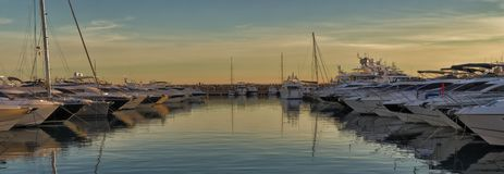 Boats in mediterranean port at sunset, reflections on water and beautiful sky, portal portals, mallorca, spain royalty free stock photos