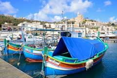 Boats in Mgarr harbour, Gozo. Traditional fishing boats in the harbour with the Our Lady of Lourdes church on the hillside to the rear, Mgarr, Gozo, Malta Stock Image