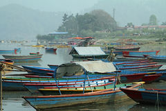 Boats in the mist. Wooden fishing boats in the morning mist at a lake harbor in Nepal Stock Image