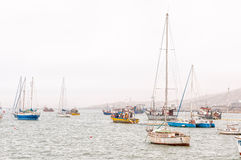 Boats in misty conditions at the harbor in Luderitz Stock Images