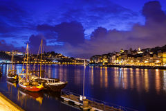 Boats moored along the riverfront with lights reflecting in the Douro River in Porto, Portugal Royalty Free Stock Photography
