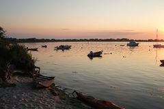 Boats moored by beach at sunset Stock Image
