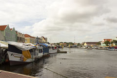 Boats moored behind iconic colorful buildings of Curacao and the Floating Market. Stock Photo