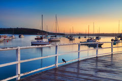 Boats moored bobbing in the waters at sunrise Stock Photos