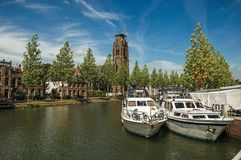 Boats moored on the canal margin, trees and brick buildings under a sunny blue sky at Weesp. Quiet and pleasant village full of canals and green near Amsterdam Stock Photos