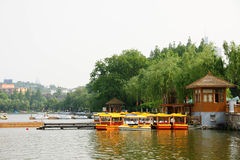 Boats moored on Chinese lake. Scenic view of pleasure boats moored on pier of lake in China Stock Image