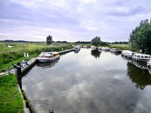 Boats moored each side of river early evening, with anglers Stock Photo
