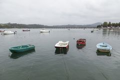 Boats moored in the estuary of San Vicente de la Barquera, Canta. Four small boats in the foreground, moored with ropes, San Vicente de la Barquera, Cantabria Stock Images