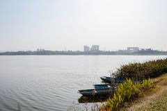 Boats moored at lakeside in sunny winter afternoon. Boats moored at grassy lakeside in sunny winter afternoon,Chengdu,China royalty free stock image