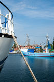 Boats moored in the harbor, island Moen, Denmark. Boats moored in the harbor on the Island of Moen, Denmark with a mooring hawser in the foreground and view of Royalty Free Stock Images