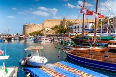 Boats moored in Kyrenia Girne harbour with fortress on backgro Royalty Free Stock Photography