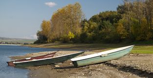 Boats moored on lake. Three wooden boats moored on lake Liptovska Mara with forest in background, Slovakia Royalty Free Stock Images