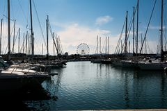 Boats moored in the marina of Pescara at sunset and the Ferris w. Some Boats moored in the marina of Pescara at sunset and the Ferris wheel background Royalty Free Stock Images