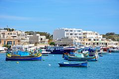 Boats moored in Marsaxlokk harbour, Malta. Traditional Maltese Dghajsa fishing boats in the harbour with waterfront buildings to the rear, Marsaxlokk, Malta Stock Images