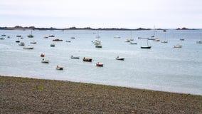 Boats moored near pebble beach in Ploubazlanec. Travel to France- many boats moored near pebble beach Plage de la Baie de Launay in Ploubazlanec commune in the Royalty Free Stock Photo