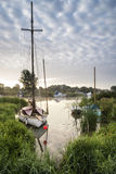 Boats moored on riverbank at sunrise in countryside landscape Stock Photo