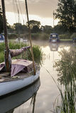 Boats moored on riverbank at sunrise in countryside landscape Stock Image