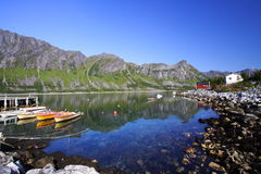 Boats moored in Senja Bay. Scenic view of boats moored in Senja Bay with mountain range and blue sky reflected on sea, Senja Island, Norway Royalty Free Stock Images