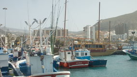 Boats moored to the jetty. Town in the background stock footage