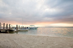 Boats moored to pier at sundown Royalty Free Stock Images