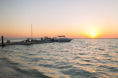 Boats moored to pier at sundown Stock Image