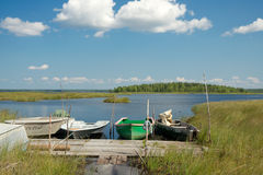Boats moored to a wooden planked footway, Karelia region, Russia Royalty Free Stock Photo