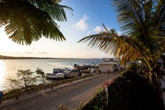 Boats moored on tropical beach with palm trees. Boats moored on tropical beach with sun rise or sun set skies illuminating palm trees. A small empty road runs Stock Photos