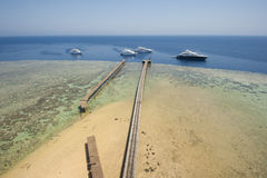 Boats moored on a tropical reef Stock Images