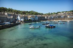 View of Mousehole village and harbour Cornwall England. Boats moored in a turquoise water of Mousehole harbour with surrounding buildings Royalty Free Stock Photo