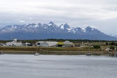 Boats in Ushuaia Harbor with the airport in the background. Boats moored in Ushuaia Harbor, Argentina, with the airport and snow covered peaks in the background Royalty Free Stock Images