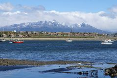 Boats moored in Ushuaia Harbor. Argentina, with snow covered peaks in the background Stock Photo