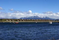 Boats moored in Ushuaia Harbor. Argentina, with snow covered peaks in the background Stock Photos