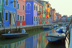 Boats moored on the waterway and reflection on the water. Burano, Venice Italy Boats moored on the waterway and reflection on the water of the colorful houses Royalty Free Stock Photo