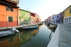 Boats moored on the waterway and reflection on the water of the. Colorful houses of the island of Burano near Venice in Italy Stock Image