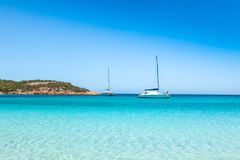 Boats mooring in the turquoise water of  Rondinara beach in Cors Royalty Free Stock Photo