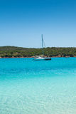 Boats mooring in the turquoise water of  Rondinara beach in Cors Stock Image