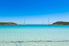 Boats mooring in the turquoise water of  Rondinara beach in Cors Stock Photos